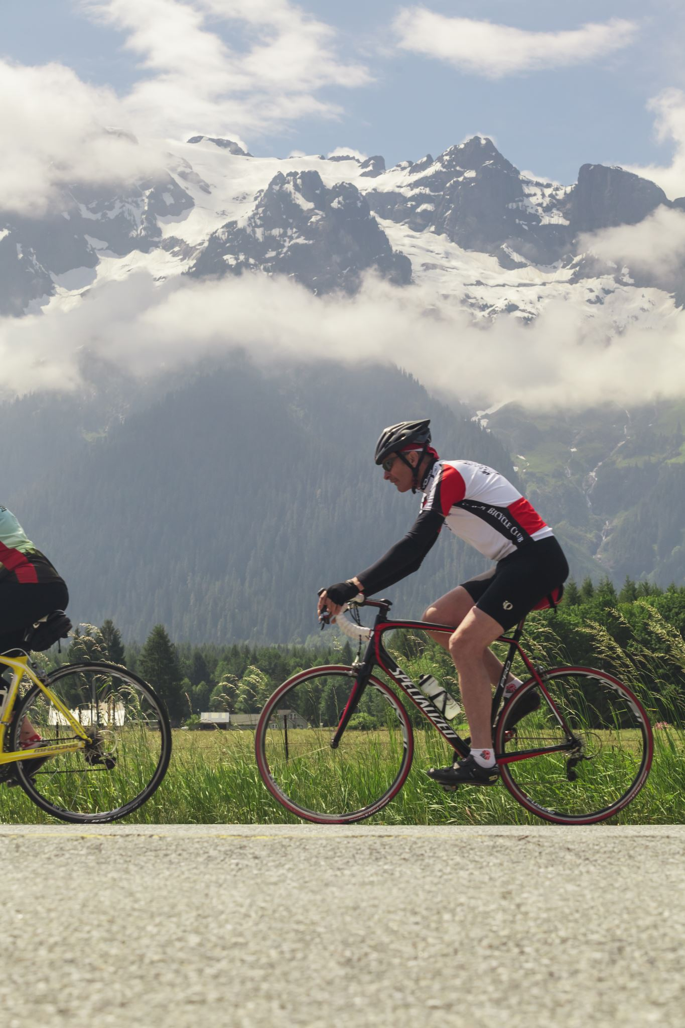 Two cyclists on road bikes in front of mountain